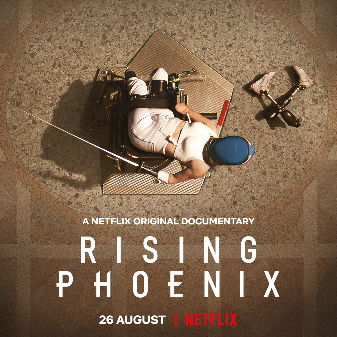 "A Paralympic fencer who is light skinned, in her gear, sits in her wheelchair and looks up to the sky. Her prosthetic legs are on the ground. White text superimposed on the photo that reads ""A Netflix Original Documentary Rising Phoenix 26 August Netflix"
